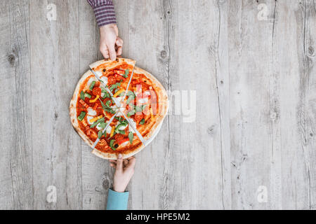 Friends sharing a delicious pizza on a rustic table, they are holding a slice, top view - Stock Photo