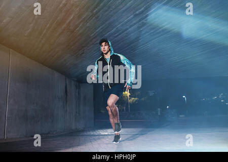 Full length shot of young athlete running under bridge in city. Fit young man jogging in the city. - Stock Photo