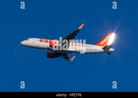 passenger airplane taking off in front of a blue background (sky) - Stock Photo