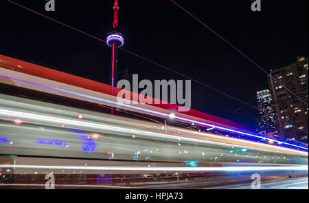 Toronto CN Tower by Night with a street car passing by creating light trails in dark sky (matching colors with CN - Stock Photo