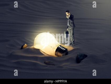 Businessman finding a light bulb in the dark. - Stockfoto