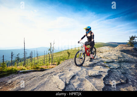 Female MTB mountain biker enjoys the view during sunny day in Mountains - Stock Photo