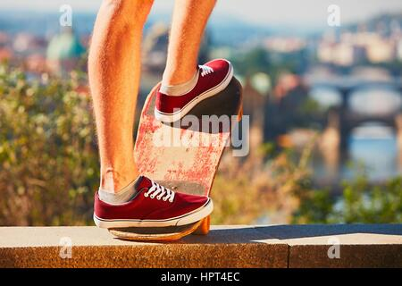 Young skateboarder is riding on the skateboard in the city. Prague, Czech Republic. - Stock Photo
