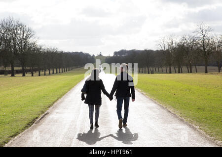 Windsor, UK. 24th February, 2017. A man and a woman walk hand in hand in fine weather on the Long Walk in Windsor - Stock Photo