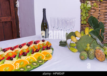 Composition of fruit and cut glass demijohn coated for wine wicker. On a table laden with a restaurant, with grapes, - Stock Photo