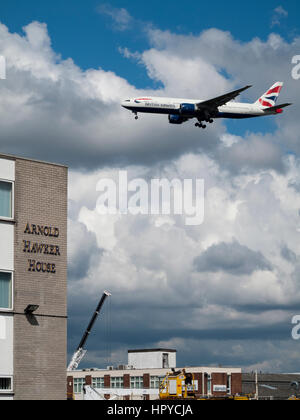 Airplane low over rooftops on approach to land at Heathrow Airport - Stock Photo
