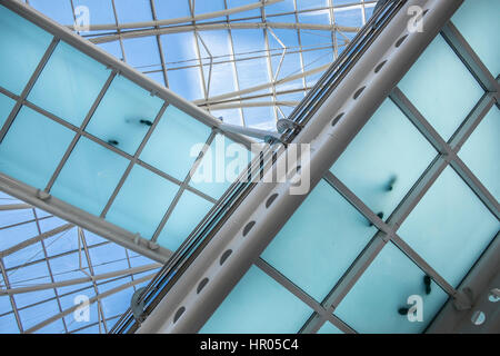modern office building with diagonal crossing transparent bridges  with footprints from people standing on it. - Stock Photo