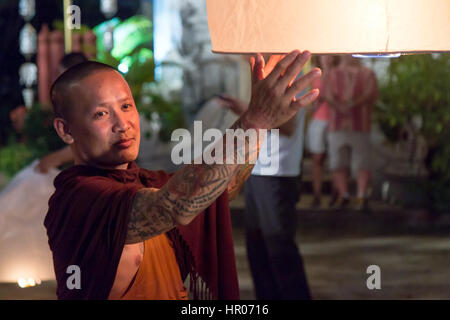 Buddhist monk holds a traditional floating lantern with a candle at night. Night celebration in a Buddhist temple, - Stock Photo
