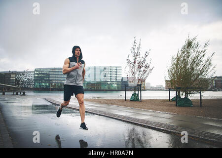 Young sportive male in sportswear with hood on running in rain on street. - Stock Photo