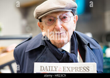 Portrait of a cloth cap wearing white old man holding up a copy of the Daily Express, a typical pensioner newspaper - Stock Photo