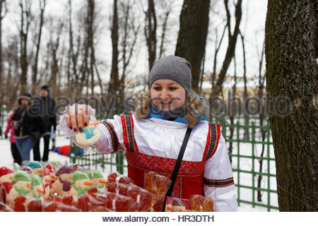 St. Petersburg, Russia, 26th February, 2017. Woman selling sweets on stick during Shrovetide celebrations in the - Stock Photo