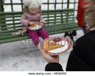 St. Petersburg, Russia, 26th February, 2017. People eating blinis during Shrovetide celebrations in the Summer Garden. - Stock Photo