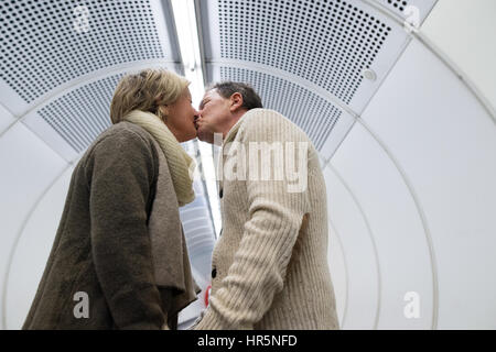 Beautiful senior couple walking in the hallway of subway in Vienna pulling a trolley luggage, kissing. - Stock Photo