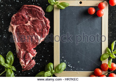 Fresh steak with spices, tomatoes and leafs of basil on marble background. Uncooked meat. Copy space. Top view - Stock Photo