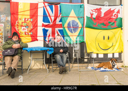 Two senior men sitting together drinking mugs of tea outside a shop selling flags on Ramsgate seafront, Kent. - Stock Photo
