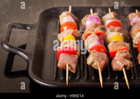 Fresh turkey meat skewers with cherry tomatoes, pepper and onion cooking on grill pan - Stock Photo