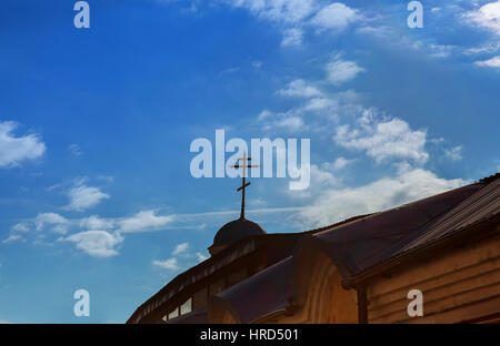 Golden Christian Cross on a dome of an Eastern Orthodox Church with a cloudy blue sky in the background - Stock Photo