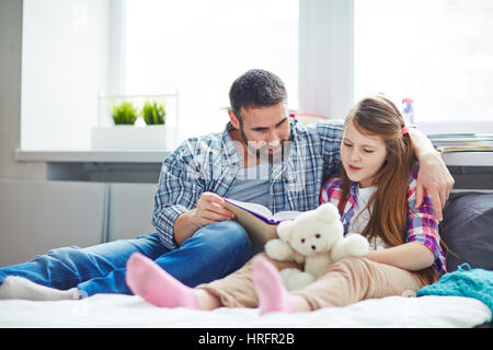 Full-length portrait of pretty family: little girl holding teddy bear in hands while reading adventure story to - Stockfoto