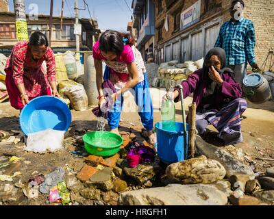 Sankhu, Central Development Region, Nepal. 2nd Mar, 2017. Women do their laundry, while others line up for drinking - Stock Photo