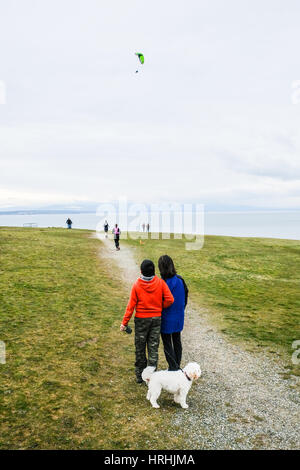A Lone Moter Glider in the Sky Above Sea with People Watching - Stock Photo