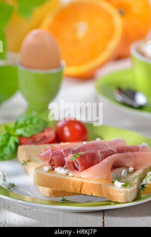 Breakfast with ham toast, a boiled egg, orange juice and a cup of cappuccino - Stock Photo