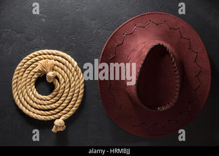 cowboy hat and lasso on black background texture - Stock Photo
