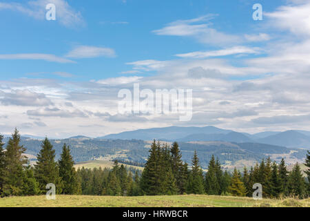 Mountains range with green meadow and storm clouds in the evening - Stock Photo
