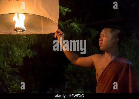 Buddhist monk holds a traditional floating lantern with a candle at night.Night celebration in a Buddhist temple, - Stock Photo