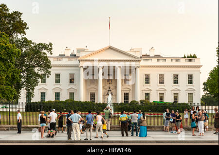 Tourists stand in front of the White House in Washington, D.C., USA. - Stock Photo