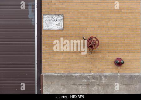 brick wall with McAvity valves - Stock Photo