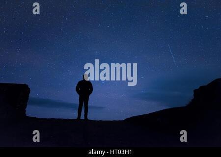 Man standing under stars at night - Cornwall, UK - Stock Photo
