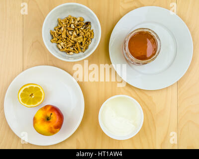 Four ingredients for a healthy and nutritious snack or smoothie, apple lemon fruit, cottage cheese, honey, shelled - Stock Photo