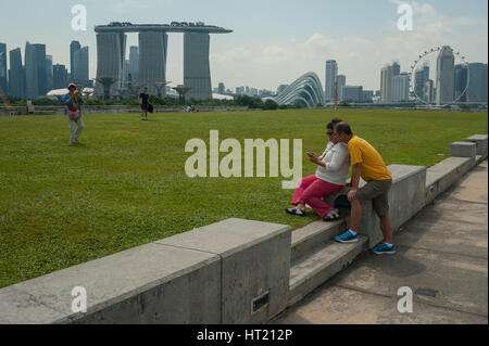 24.09.2016, Singapore, Republic of Singapore - Visitors on the Marina Barrage rooftop garden with the Marina Bay - Stock Photo