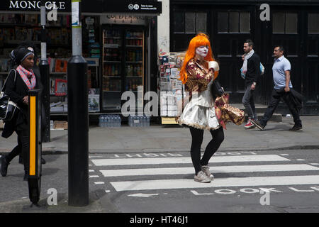 LONDON, ENGLAND - 31st October, 2016 The girl with red hair on Halloween crossing the road at a pedestrian crossing - Stock Photo