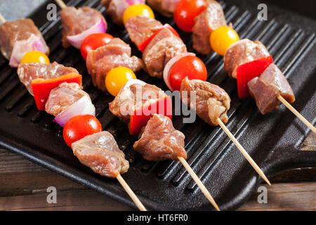 Raw turkey meat skewers with cherry tomatoes, pepper and onion on grill before cooking - Stock Photo