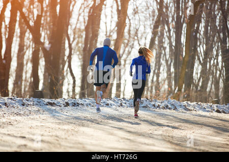 Two persons jogging in nature together, back view - Stock Photo