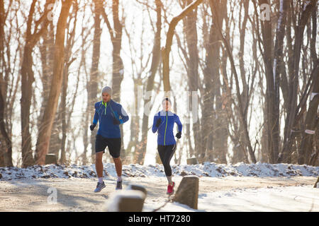 Two person jogging in nature in the winter - Stock Photo