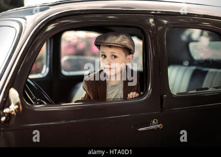 Portrait of a little boy sitting on the front seat of a retro car looking at the camera - Stock Photo