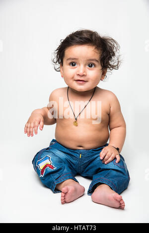 Indian baby boy playing over over white background and looking at camera - Stock Photo