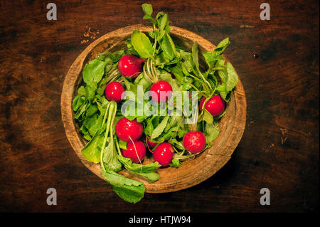 Top view of fresh organic radish in a plate on wooden table - Stock Photo