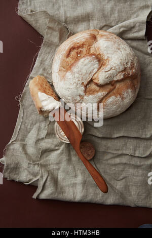 Top view of fresh bread and knife with butter on vintage cloth - Stock Photo