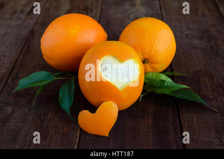 A few ripe oranges with leaves on a dark wooden background. One cut orange peel in the shape of a heart. - Stock Photo