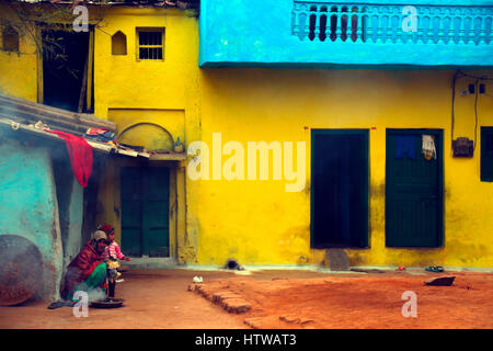 An Indian woman with the daughter in a colourful shawl sits outside her house, Khajuraho, India - Stock Photo