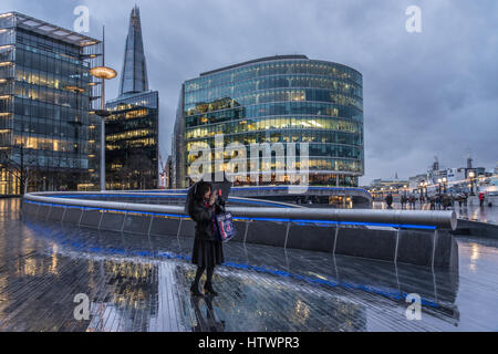 Woman taking a selfie outside in the rain under umbrella in London with view of The Shard in the City. - Stock Photo