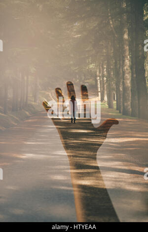 Double exposure of a hand and a woman walking away - Stockfoto