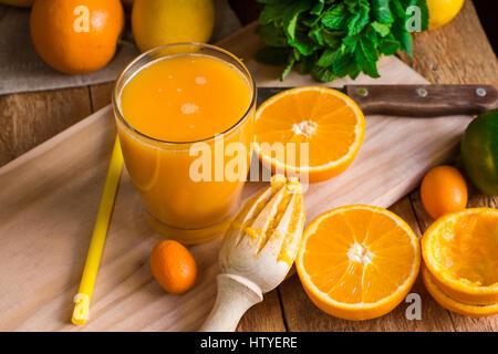 Citrus fruits oranges lemons lime cumquat, fresh mint, reamer, freshly pressed juice in glass on wood kitchen table - Stock Photo