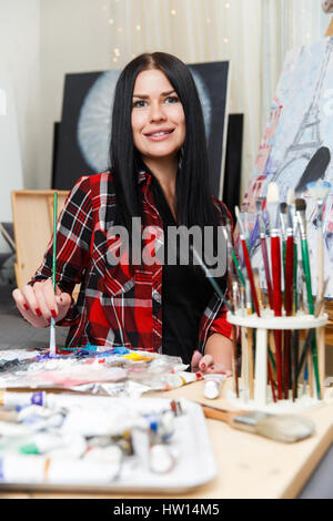 Long-haired painter in checkered shirt - Stock Photo