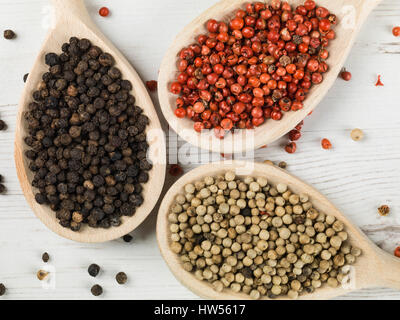 Whole Red White and Black Pepper Corns Against a White Background - Stockfoto