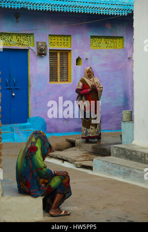 indian women talking in a colorful street, Kharujaho, india - Stock Photo