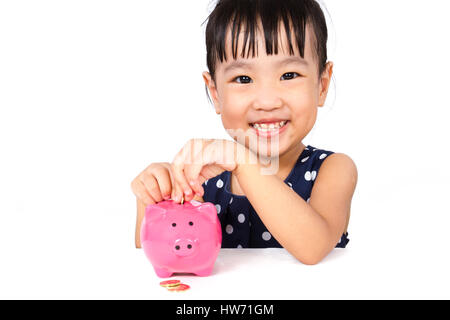 Asian Little Chinese Girl Putting Coins into Piggy Bank isloated on White Background - Stock Photo